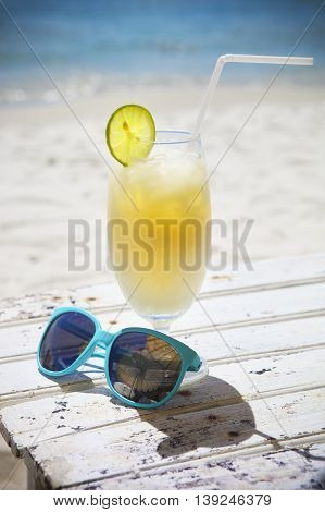Fresh tropical cocktail with rum and blue sunglasses on beautiful sunny beach