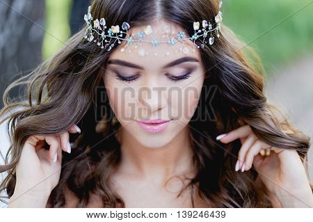 Close-up portrait of beautiful young brunette European type, with long curly hair and the decoration on the hair