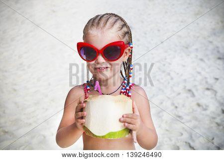 Cute little with dreadlocks girl drinking coconut cocktail on tropical beach. Beach holidays concept
