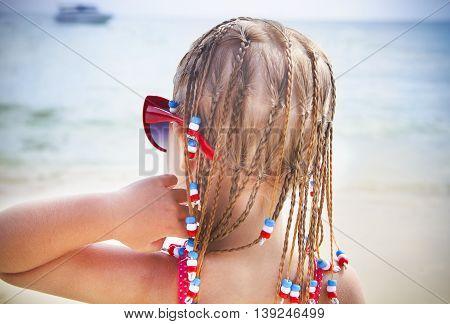 Cute little with dreadlocks girl on tropical beach. Beach holidays concept