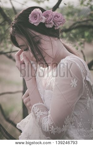 young woman portrait  in white lacy dress and roses in hair closeup