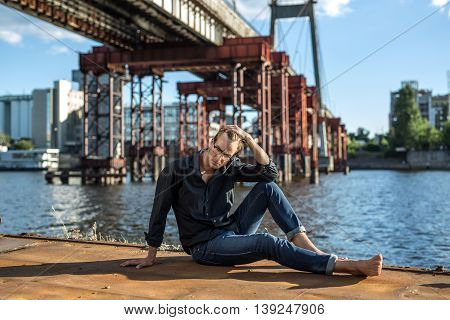 Pensive barefoot guy in glasses sits on the quay on the background of the river and the bridge. He wears blue jeans and a dark shirt. Male looks down. Outdoors. Horizontal.