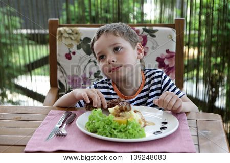 Boy eating chicken leg in a cafe