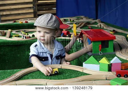 Child playing with toy railroad in park
