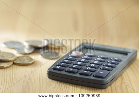 Calculator And A Stack Of Coins On A Wooden Table