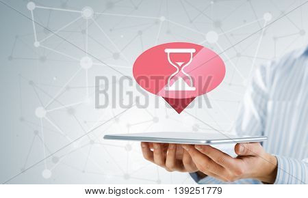 Businessman holding tablet computer and loading icon on screen
