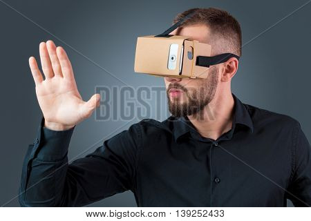Excited young man using a VR headset glasses and experiencing virtual reality on grey blue background