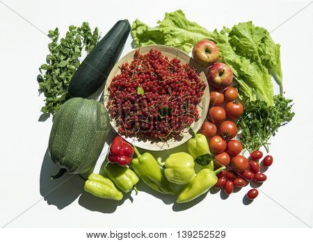 Fresh summer vegetable and fruit harvest from garden. Top view on multiple kinds of vegetables on white background.