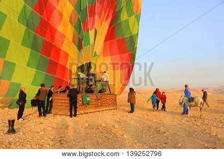 VALLEY OF THE KINGS EGYPT - MAY 17 2016: People dismounting a Hot air balloon in the morning sun in the Valley of the Kings Egypt Africa