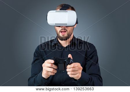 Excited young man using a VR headset glasses and experiencing virtual reality on grey blue background. with a joystick in their hands