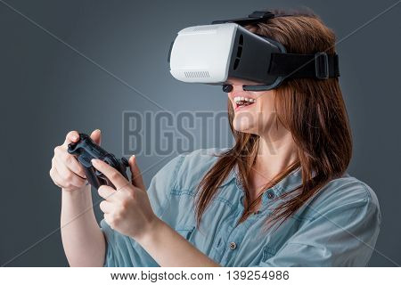 Excited young woman using a VR headset glasses and experiencing virtual reality on grey blue background. with a joystick in their hands