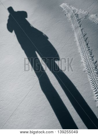 Automobile tire footprint and shadow of a man in the snow