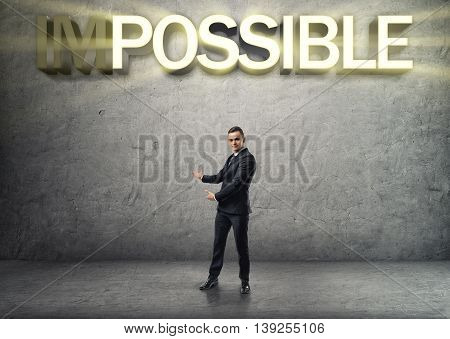 Businessman stands showing the word by both hands on the concrete background. Everything is possible. Inspiration and ideas. Hard work. Office clothes.