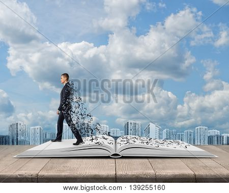 Side view of young businessman walking on an open book with a plume of letters. Gaining knowledge. Useful information. Business reading. Office clothes. Education concept.