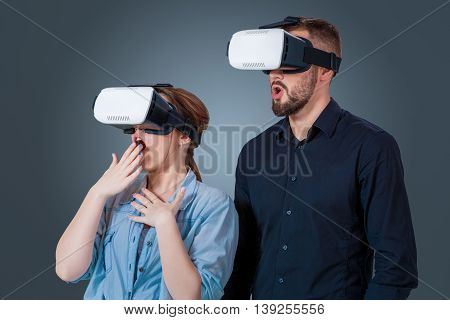 Excited young couple using a VR headset glasses and experiencing virtual reality on grey blue background
