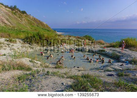 Russia Krasnodar region - Black sea 21.07.2016: People take a mud bath of blue clay in Inal Bay on the Black Sea