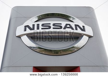 Ulyanovsk Russia - July 20 2016: Promotional stand with NISSAN sign near building Nissan service center which provides vehicle maintenance repairs and diagnostics.