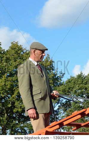 IPSWICH SUFFOLK UK 25 October 2014: East Anglia Equestrian Fair English countryman holding reins of Carthorse