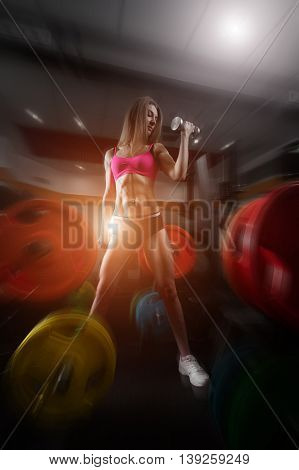 Fitness woman in the gym. fitness girl with dumbbell posing in the gym. Perfect fitness body. Fitness - concept of healthy lifestyle.