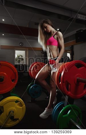 Fitness woman in the gym. Fitness girl with shaker posing in the gym. Fitness - concept of healthy lifestyle. Perfect fitness bikini body. Bodybuilder woman in the gym.