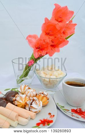 Sweets for the coffee - biscuits sprinkled with condensed milk powder, sugar cubes and a cup of coffee