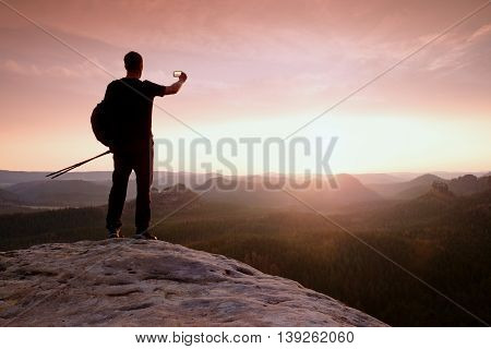 Tourist Guide Proped Against Pole In Hand. Hiker With Sporty Backpack
