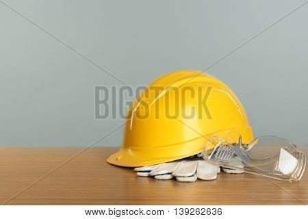 Construction tools and helmet on wooden table