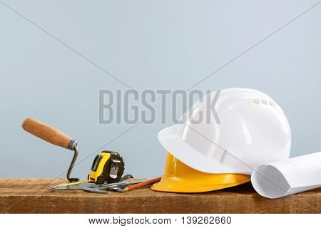 Construction blueprints with tools and helmets on light background