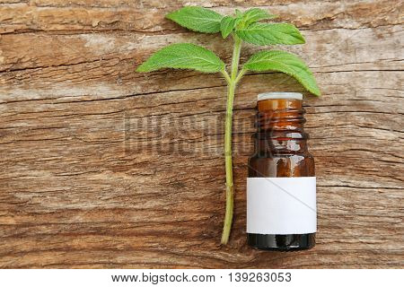 Dropper bottle and herbs on wooden background