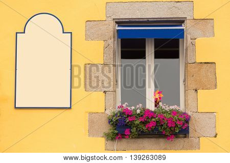 Traditional window flowered with geranium with copyspace in Brittany, France