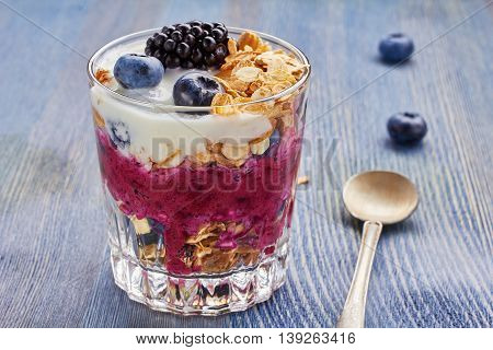 Yogurt dessert with cherry, blueberries, balckberries and muesli on blue wooden table.