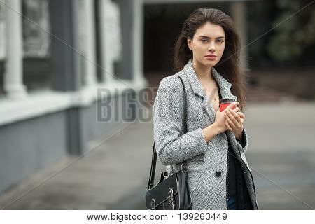 Lifestyle Fashion Portrait Of Beautiful Young Brunette Woman In Grey Coat With Coffee Cup Posing On