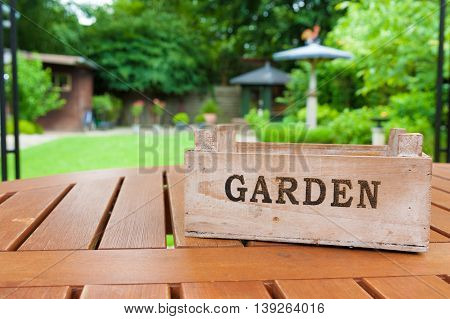 Tray With Word Garden On A Table With A Garden In The Background