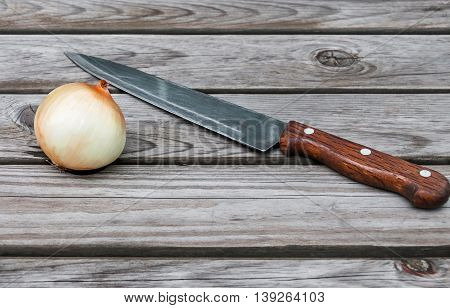 Knife, onion  on a table made of wooden planks