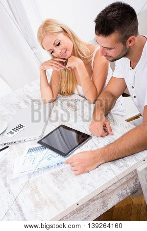 A beautiful young couple sitting at a Table discussing business.