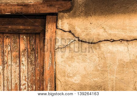 Cracked Lime Stone Wall And Detail Of An Old Wooden Door