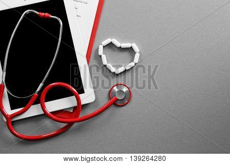 Red stethoscope with tablet on grey table