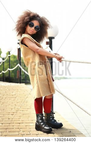 African American  little girl wearing stylish clothes outdoors. Fashion kid concept