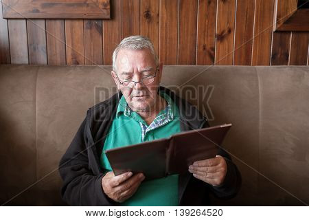 Sober Senior Man Reading A Restaurant Menu