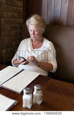 Restrained Senior Woman Reading Messages On Her Smartphone