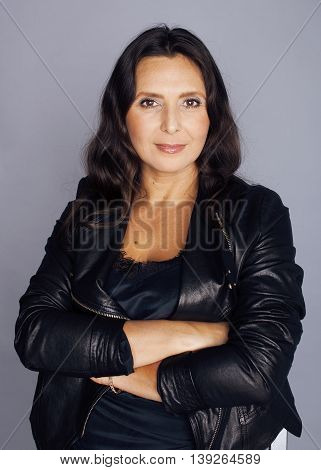 pretty brunette confident stylish real mature woman sitting on chair in studio, sexy on gray background wearing leather jacket, middle age concept