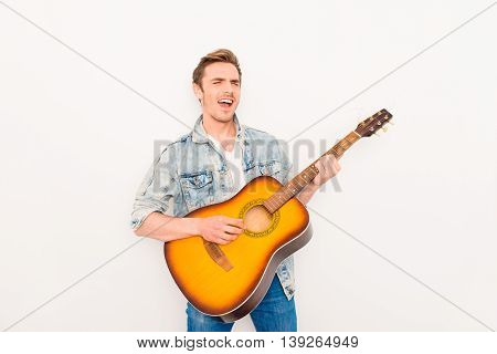 Young Musician Playing On The Guitar And Singing On White Background