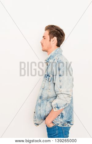 Side View Photo Of Stylish Man In Jeans Jacket Holding Hands In Pocket