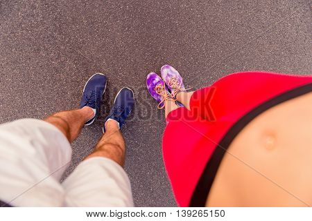 Top View Photo Of Man And Woman Legs In Sneakers After Training