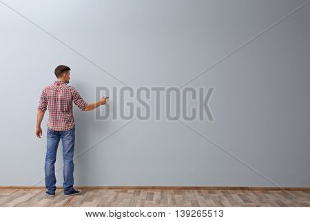 Man writing something on grey wall