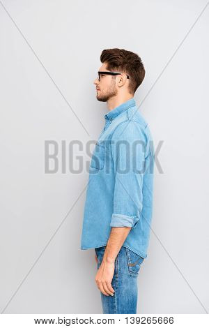 Side View Portrait Of Young Guy In Glasses And Blue Shirt