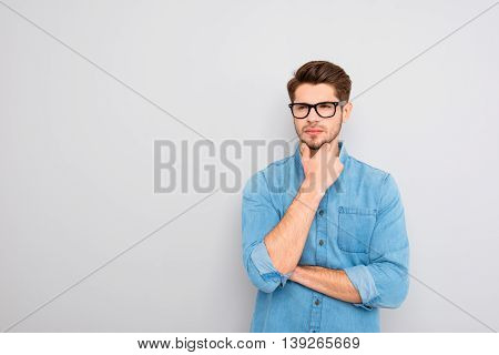 Portrait Of Handsome Minded Young Man In Glasses Think