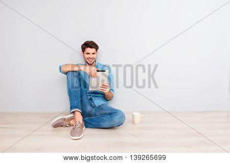 Happy Guy Sitting On Floor With Tablet And Reading