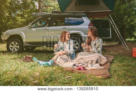 Happy young women friends resting sitting under a blanket in campsite into the forest