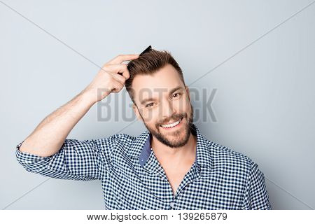 Portrait Of Happy Smiling Handsome Guy Combing His Hair